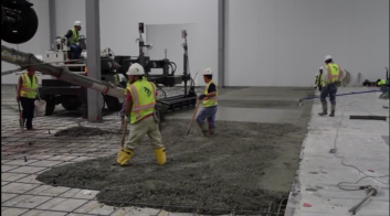 Frick floor construction strike-off with laser screed and laborers installing floor.