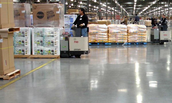 Photo of forklift in large warehouse pulling heavy load over durable Fricks floor.
